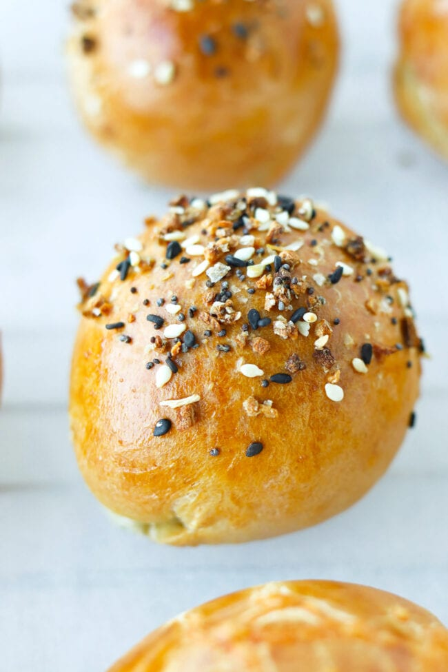 Close-up front view of a baked bagel ball topped with Everything Bagel Seasoning on parchment paper.