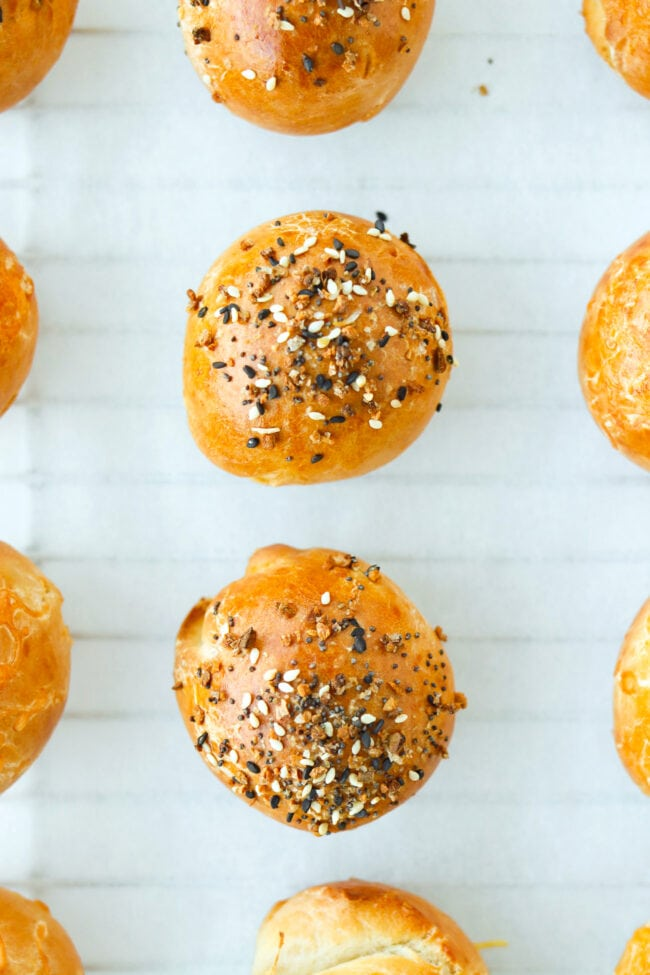 Close-up top view of baked stuffed bagel bombs on parchment paper.