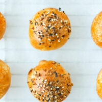 """Top view of baked bagel bombs on nonstick cooking paper. Text overlay """"Greek Yogurt Dough Stuffed Bagel Bombs"""" and """"thatspicychick.com""""."""