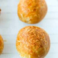 """Front view of bagel bomb on parchment paper. Text overlay """"Easy Homemade Stuffed Bagel Bombs"""" and """"thatspicychick.com""""."""