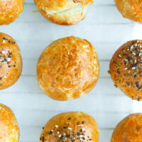 Top view of stuffed bagel bombs on sheet of parchment paper.