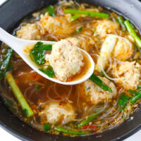 Front view of bowl with a spoon, noodle soup, meatballs, and fresh herbs.