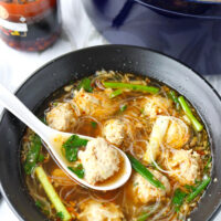 """Front view of spoon with a meatball and soup in bowl of noodle soup. Text overlay """"Thai Glass Noodle Soup with Chicken & Prawn Meatballs"""" and """"thatspicychick.com""""."""
