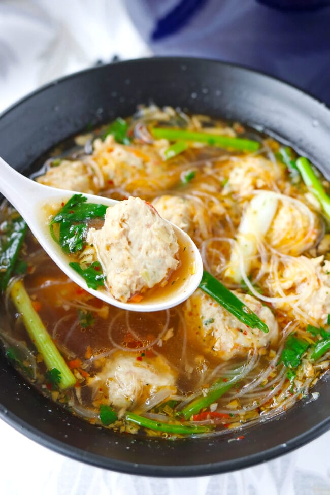 Noodle soup with meatballs in a bowl, and spoon in bowl with a meatball on top.