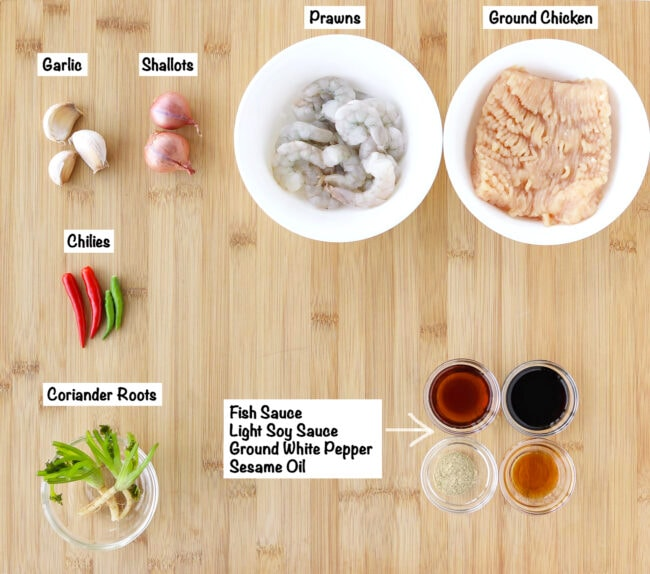 Labeled ingredients for chicken and prawn meatballs on a wooden board.