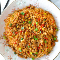 """Top view of plate with stir-fried vermicelli and pork. Text overlay """"Ants Climbing A Tree"""", """"Sichuan Glass Noodles Stir-fry"""", and """"thatspicychick.com""""."""