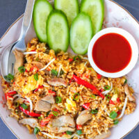 """Close-up top view of fried rice on a plate with utensils, cucumber, and Sriracha sauce. Text overlay """"Spicy Pork Fried Rice"""", """"Easy + Quick + Better Than Takeout!"""", and """"thatspicychick.com""""."""