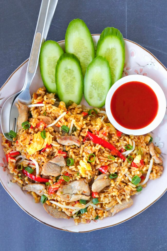 Close-up top view of pork fried rice on a plate with fork, spoon, cucumber, and Sriracha sauce.