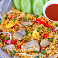 """Front view of pork fried rice on a plate. Text overlay """"Spicy Pork Fried Rice"""", """"Easy + Quick + Better Than Takeout!"""", and """"thatspicychick.com""""."""