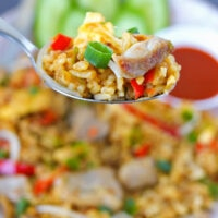 """Spoon holding up a bite of pork fried rice above plate. Text overlay """"Spicy Pork Fried Rice"""", """"Easy + Quick + Better Than Takeout!"""", and """"thatspicychick.com""""."""