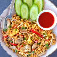 Top view of pork fried rice on a plate with fork, spoon, cucumber, and Sriracha sauce.