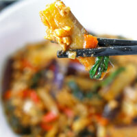 """Chopsticks holding up an eggplant strip above a bowl with a stir-fry dish. Text overlay """"Thai Eggplant Stir-fry with Thai Chili Paste, Pork & Basil"""" and """"thatspicychick.com""""."""