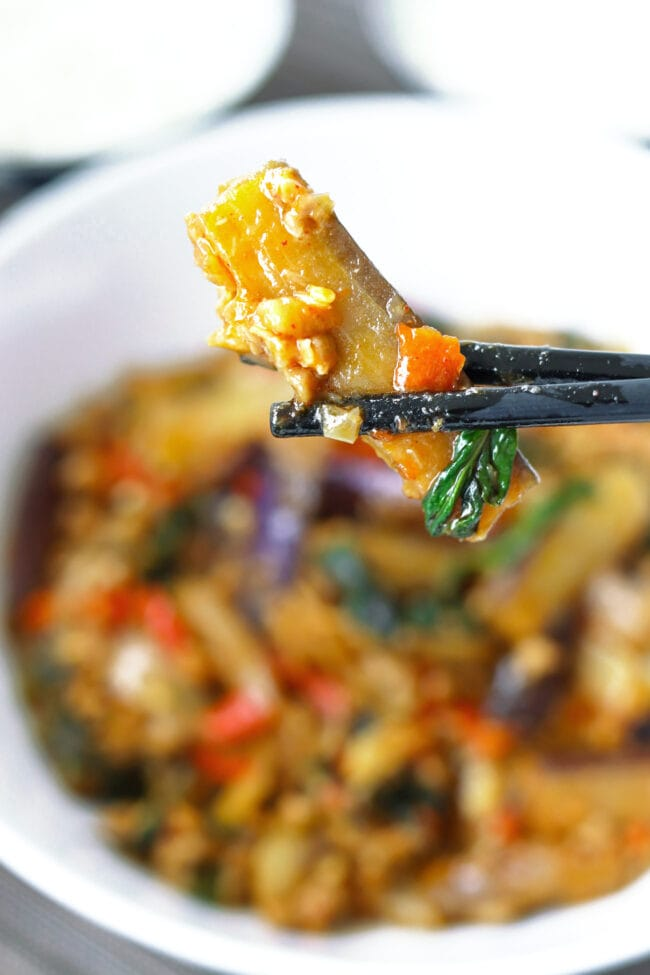 Chopsticks holding up an eggplant strip coated in sauce above a bowl with a stir-fry.