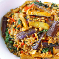"""Front view of a bowl with an eggplant stir-fry dish. Text overlay """"Thai Eggplant Stir-fry with Thai Chili Paste, Pork & Basil"""" and """"thatspicychick.com""""."""