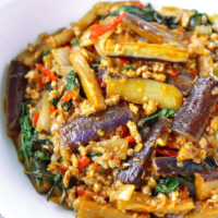 Front view of bowl with eggplant, pork, and Thai basil stir-fry.
