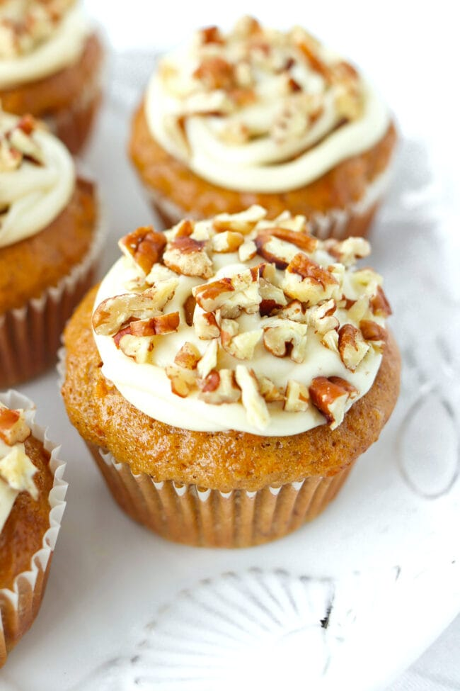 Close-up front view of carrot cake muffins on a plate.