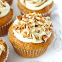 """Close-up front view of muffins on a plate. Text overlay """"Carrot Cake Muffins with Maple Cream Cheese Frosting!"""" and """"thatspicychick.com""""."""