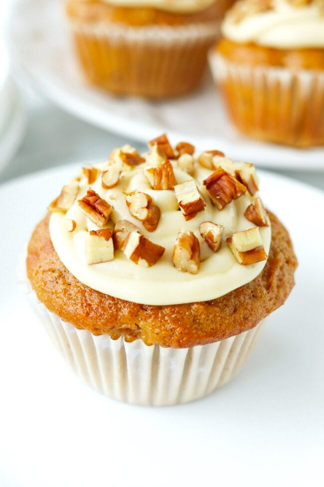 Front view of a carrot cake muffin on a plate. Muffins on a plate behind.