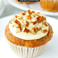 """Close-up front view of muffin on plate and muffins behind. Text overlay """"Carrot Cake Muffins with Maple Cream Cheese Frosting"""" and """"thatspicychick.com""""."""