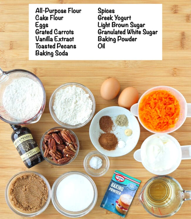 Labeled ingredients for Carrot Cake Muffins on a wooden board.