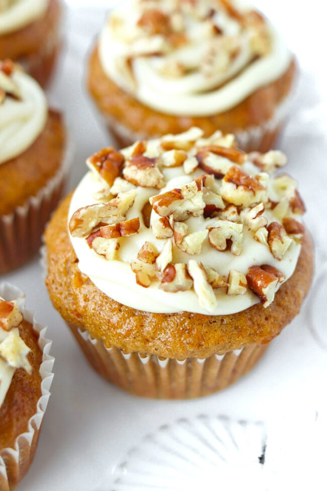 Close-up of front view of carrot cake muffins on a plate.