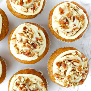 Top view of carrot cake muffins with frosting on a plate.