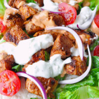 """Close-up of chicken shish with salad on a tortilla with garlic sauce. Text overlay """"Kebab Garlic Sauce"""" """"Just like your favorite kebab shop!"""", and """"thatspicychick.com""""."""