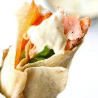"""Salmon kebab with garlic sauce wrapped in foil. Text overlay """"Kebab Garlic Sauce"""" """"Just Like Takeaway!"""", and """"thatspicychick.com""""."""