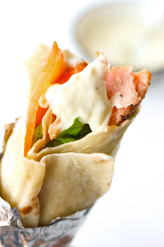 Close-up of salmon kebab with garlic sauce wrapped in foil.