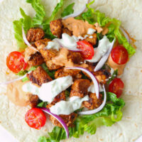 """Chicken Shish on tortilla with lettuce, red onion, cherry tomatoes, and sauces. Text overlay """"Kebab Shop Garlic Sauce"""" and """"thatspicychick.com""""."""