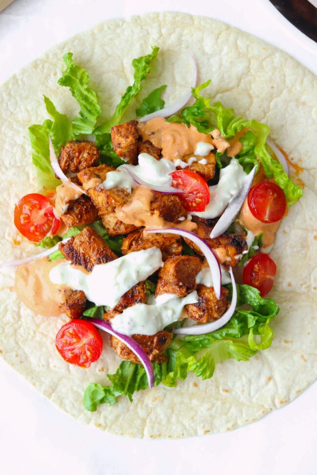 Chicken Shish on tortilla with lettuce, onion, cherry tomatoes, and sauces.