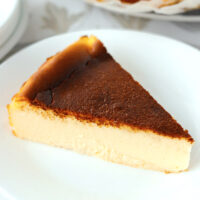 """Close-up front view of cheesecake on a plate. Text overlay """"Basque Burnt Cheesecake"""", """"Lemon Flavored"""" and """"thatspicychick.com""""."""