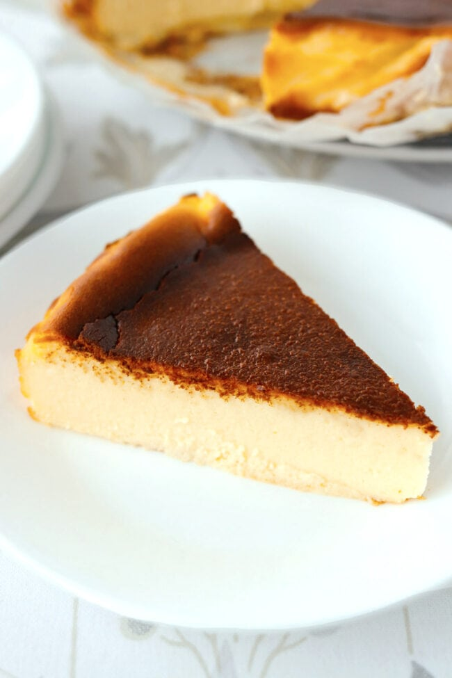 Front view of slice of Basque cheesecake on a plate. Rest of cheesecake on plate behind.