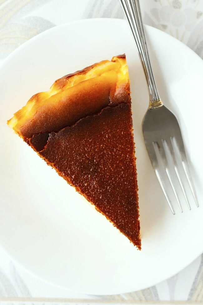 Top view of basque cheesecake slice on plate with a fork.