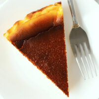 """Top view of cake slice on a plate with a fork. Text overlay """"Basque Burnt Cheesecake"""", """"Lemon Edition"""" and """"thatspicychick.com""""."""