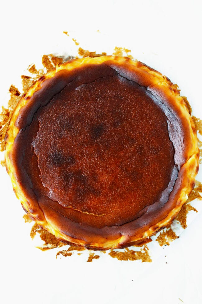 Top view of burnt basque cheesecake on a white background.