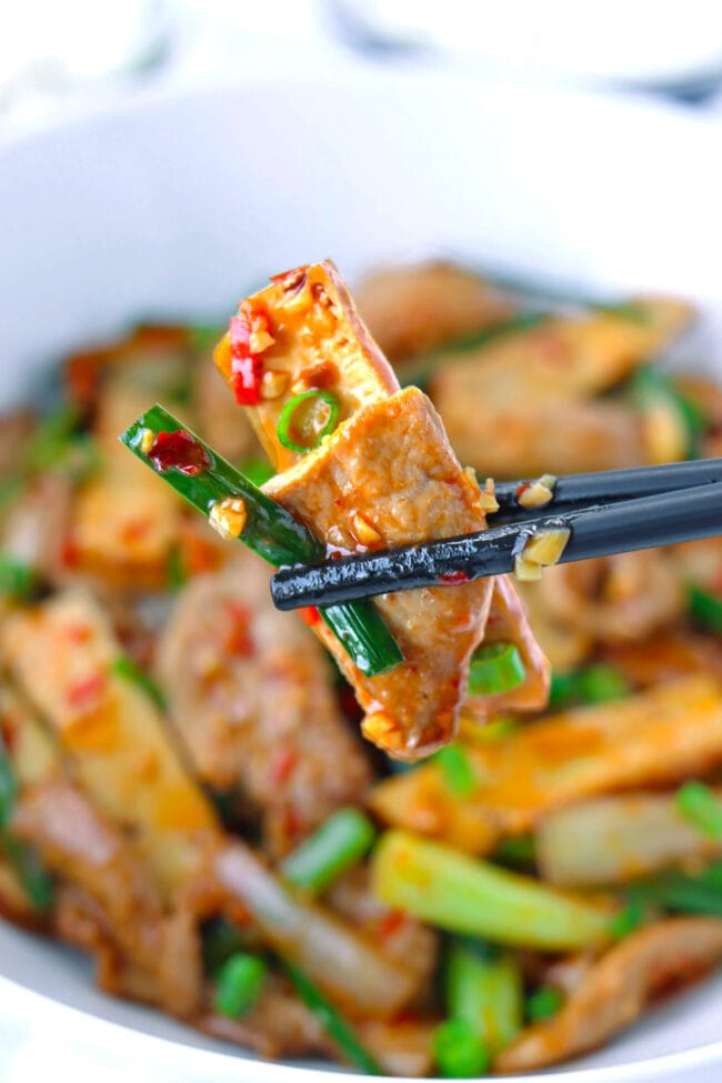 Chopsticks holding up a slice of tofu, pork, and garlic scape above stir-fry dish in bowl.