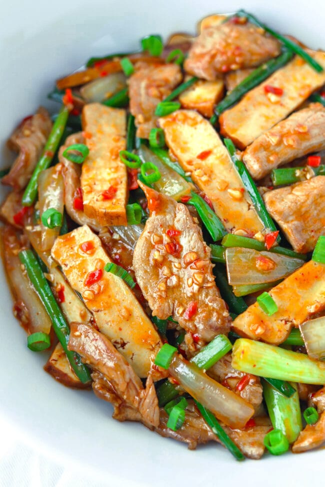 Close-up front view of pork, tofu, and garlic scapes stir-fry in a serving bowl.