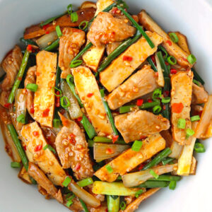 Top view of bowl with stir-fried garlic scapes, pork, and tofu.