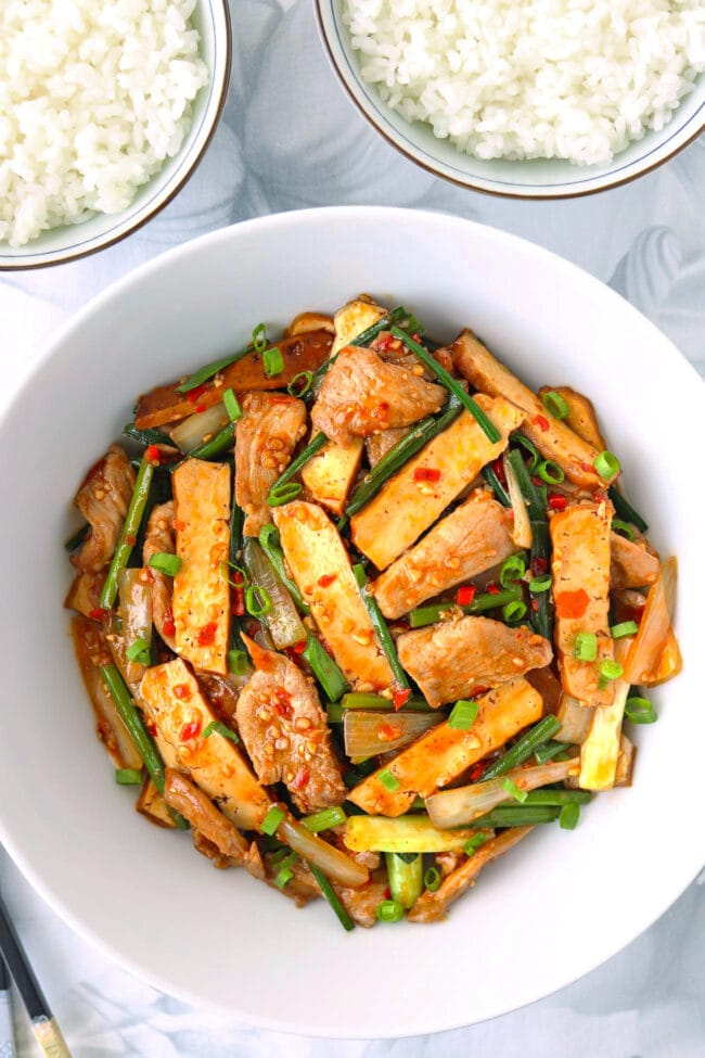 Stir-fried tofu, pork, and garlic scapes dish in serving bowl and two bowls rice above.