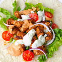 Close-up of chicken shish chunks, lettuce, sliced onion, cherry tomato halves, and sauces on a tortilla.