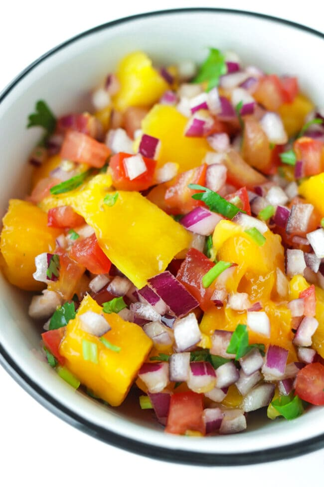 Close-up front view of mango salsa in a round bowl.