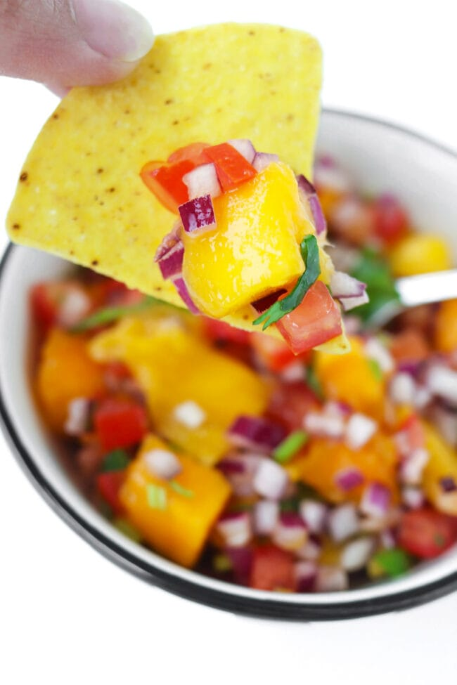 Hand holding up a tortilla chip topped with mango salsa above bowl with salsa.
