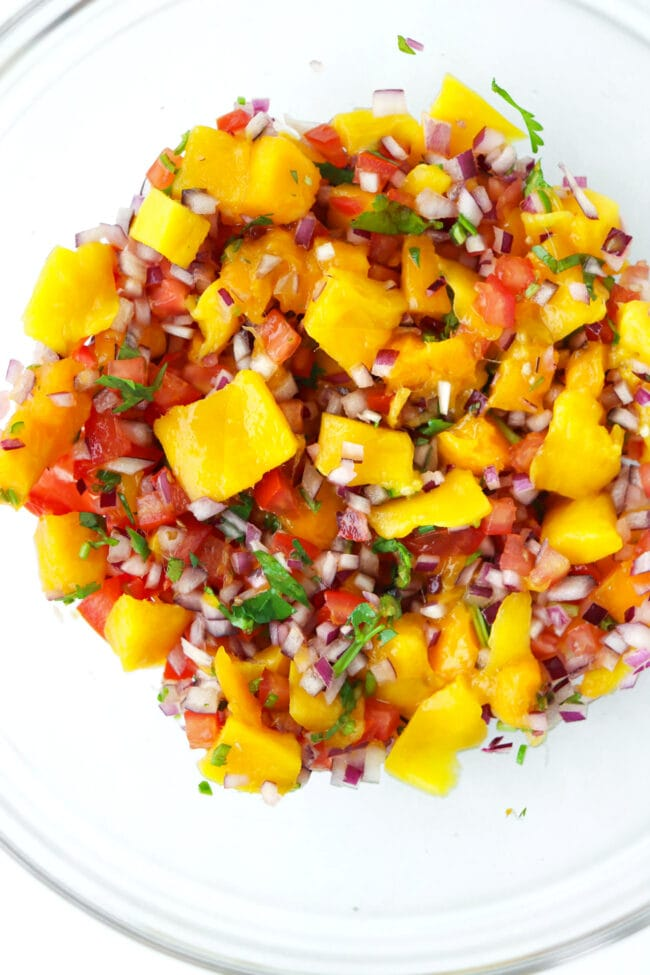 Mixing bowl with mango salsa ingredients tossed together.
