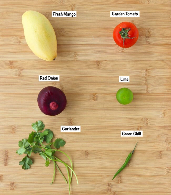 Labeled ingredients for mango salsa on a wooden board.
