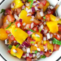 """Top view of mango salsa in a bowl with a spoon. Text overlay """"Quick Mango Salsa"""", """"Easy 