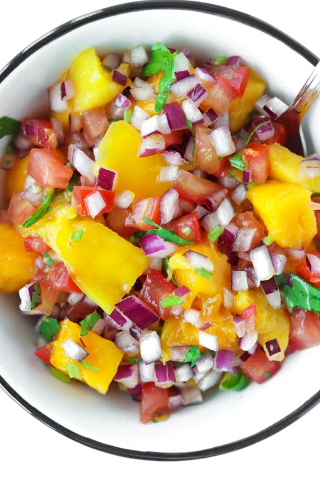 Top view of bowl with mango salsa and a spoon.
