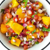 """Top view mango salsa in a bowl. Text overlay """"Easy Mango Salsa"""", """"Dip 