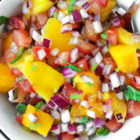"""Top view of mango salsa in a round bowl with a spoon. Text overlay """"Fresh Mango Salsa"""", """"Easy 
