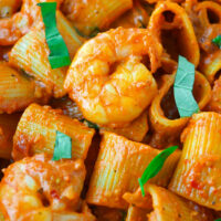 Close-up of tomato sauce pasta and prawns with sliced basil.